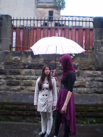 Naziyah Mahmood (Nour-el-ain) and Linn Mattisson (Lee Yoo Min) chatting on set in the rain.